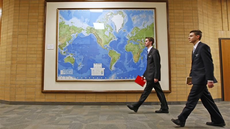 In this Jan. 31, 2008, file photo, two Mormon missionaries walk past a large map of the world in a hallway at the Missionary Training Center in Provo.